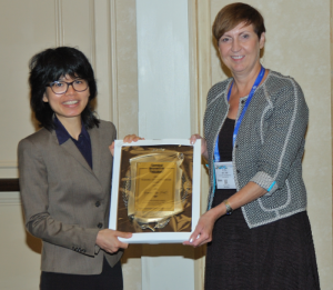 Yimon Aye receiving the CRT Young Investigator Award award from Judy Bolton